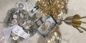 a different angle on the lot of silver coins and gold jewelry
